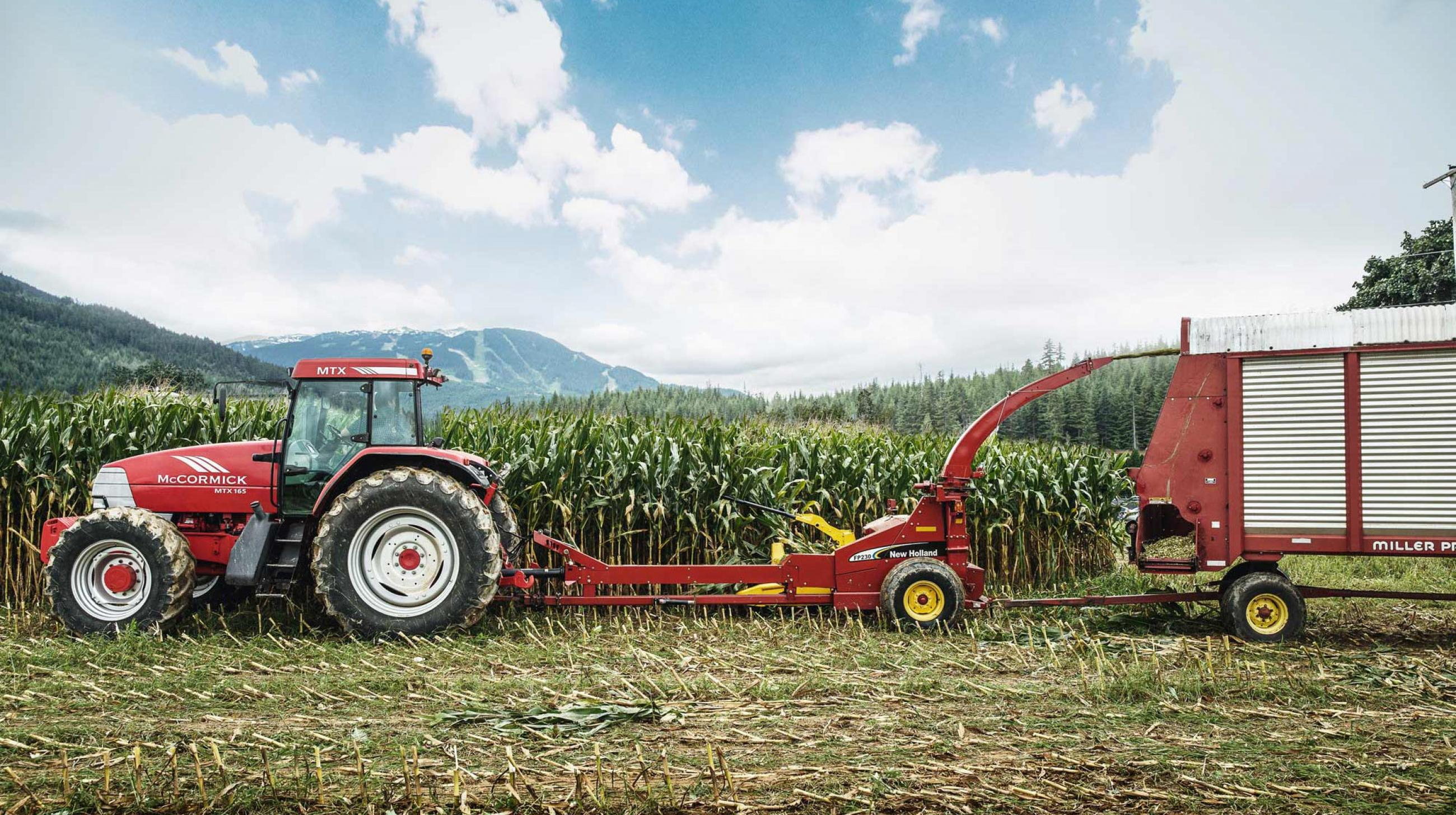 Tractor with pull behind harvester harvesting corn